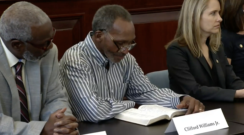 Clifford Williams, Jr. (center) reads from his Bible during the news conference announcing his exoneration. His nephew, Nathan Myers (left) was also exonerated. To their right is Shelley Thibodeau, director of the Florida Fourth Judicial Circuit State Attorney's Conviction Integrity Unit.